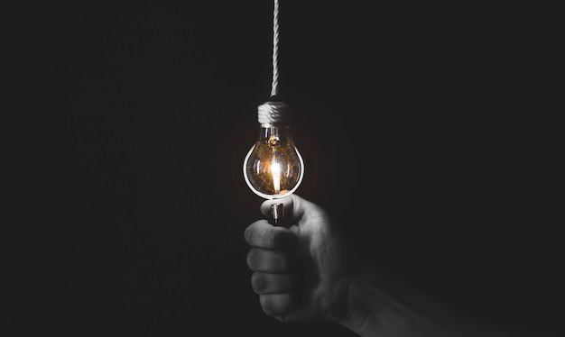 新しいアイデアのコンセプト。男は電球の近くにライトナーを持っています。黒と白の写真。