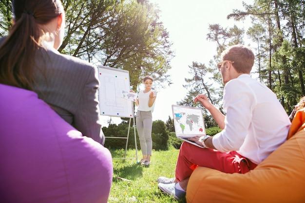 Новые идеи. решительная худенькая девушка стоит у доски и обсуждает свой проект с однокурсниками