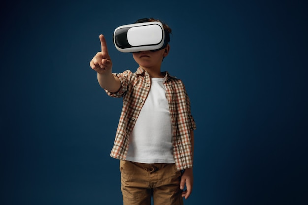 New ideas and emotions. little boy or child pointing to the empty space with virtual reality glasses isolated on white studio background. concept of cutting edge technology, video games, innovation.