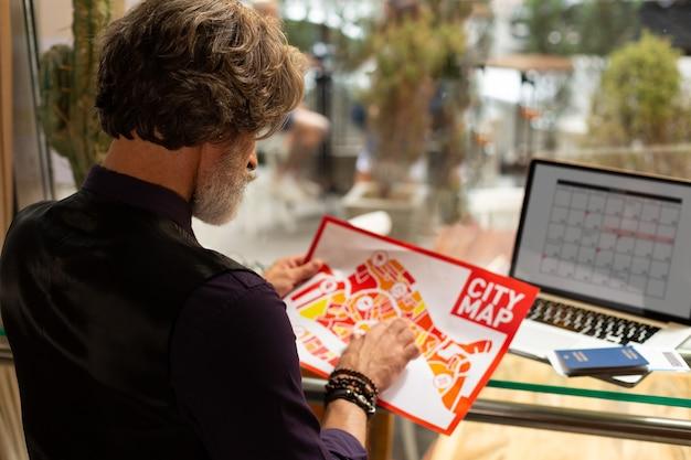 Новое в городе. сосредоточенный мужчина сидит в кафе с картой города в руках, указывая на нее, изучает карту перед прогулкой.