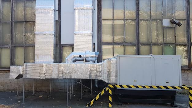 오래된 사무실 건물이나 대형 창고 근처의 새로운 산업 환기 시스템. 지상의 환기 장치.
