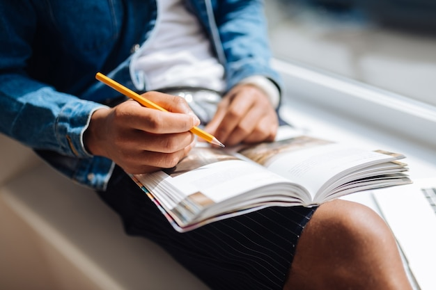 新情報。必要な記事を読みながら膝の上に本を保持しているリラックスした国際的な男