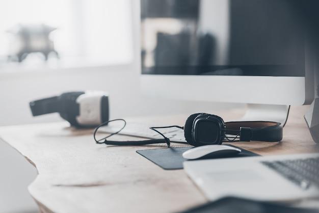 新しいイノベーション。ヘッドフォンとvrヘッドセットをオフィスの机の上、ラップトップとコンピューターの近くに置く