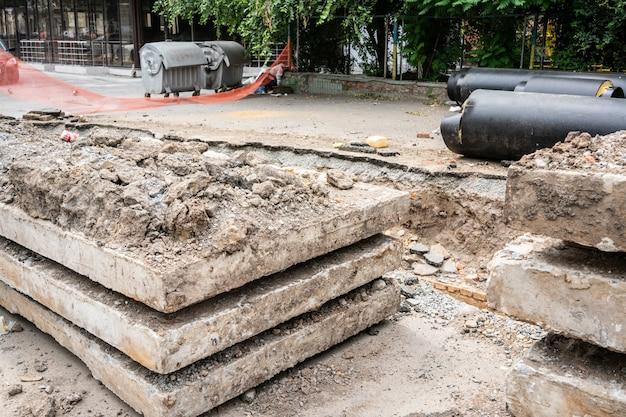 Новые изолированные черные водопроводные трубы и бетонные плиты на городской дороге в летний день. концепция инфраструктуры городской канализации, модернизация и реконструкция метрополитена.
