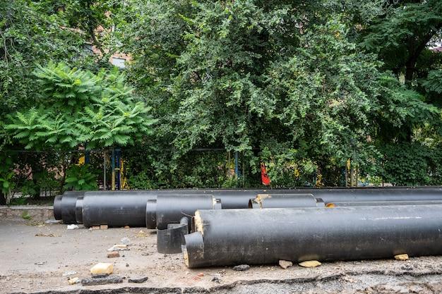 여름날 푸른 나무 근처에 야외에 누워 있는 새로운 절연된 검은 수도관. 도시 하수도 인프라 개념, 지하 시스템의 현대화 및 재건.