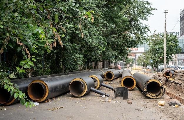 Новые изолированные черные водопроводные трубы, лежащие на открытом воздухе в летний день возле зеленых деревьев
