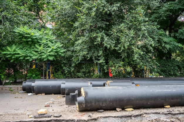 New insulated black water pipes lying outdoors in summer day near green trees. urban sewerage infrastructure concept, modernization and reconstruction of underground system.