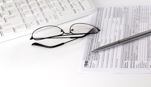 New irs 1040 tax form, instructions, pen and keyboard and glasses. copy space