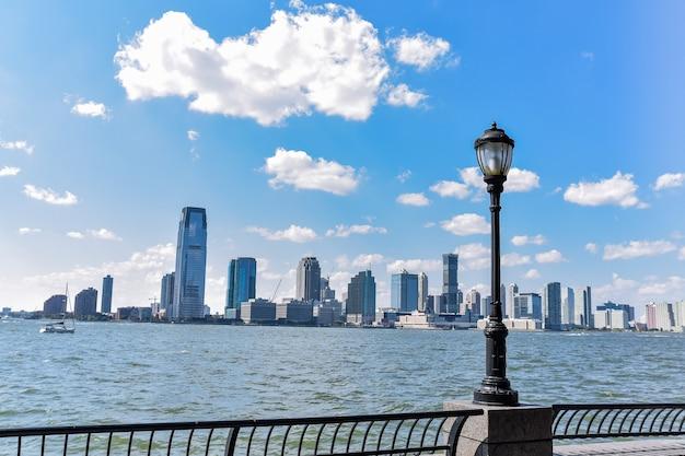 晴れた日のバッテリーパークからのニュージャージーのスカイライン。木々や街灯からの街並みの眺め。