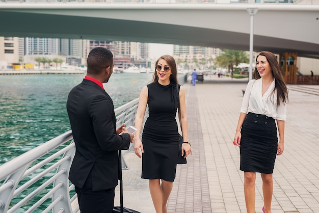 New job in a big city. two beautiful business woman meeting with their new college at dubai marine.