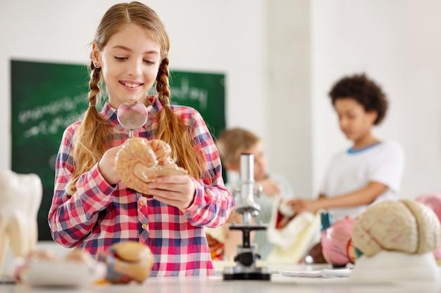 새로운 지식. 생물학에 대한 수업을하면서 돋보기를 들고 명랑 긍정적 인 소녀