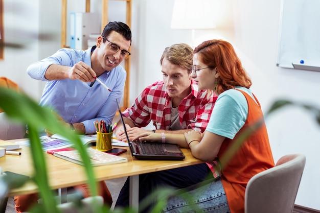 새로운 지식. 새로운 정보를 배우면서 노트북 화면을보고있는 멋진 똑똑한 사람들