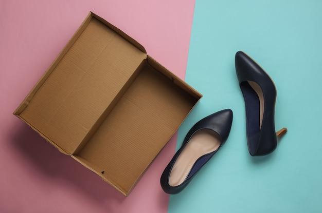 ブルーピンクのパステルカラーの背景に段ボール箱が付いた新しい革靴女性へのギフト