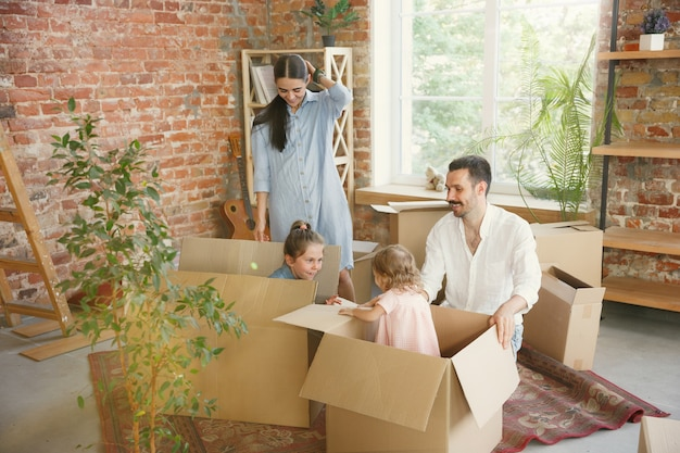New life. adult family moved to a new house or apartment. spouses and children look happy and confident. moving, relations, new life concept. unpacking boxes with their things, playing together.