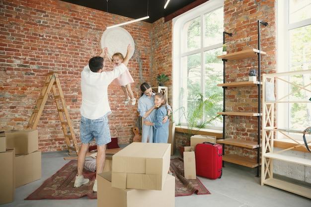 새로운 삶. 성인 가족이 새 집이나 아파트로 이사했습니다. 배우자와 자녀는 행복하고 자신감있게 보입니다. 이동, 관계, 새로운 삶의 개념. 물건으로 상자를 풀고 함께 연주합니다.