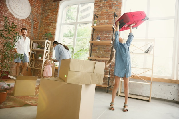 Новая жизнь. взрослая семья переехала в новый дом или квартиру. супруги и дети выглядят счастливыми и уверенными