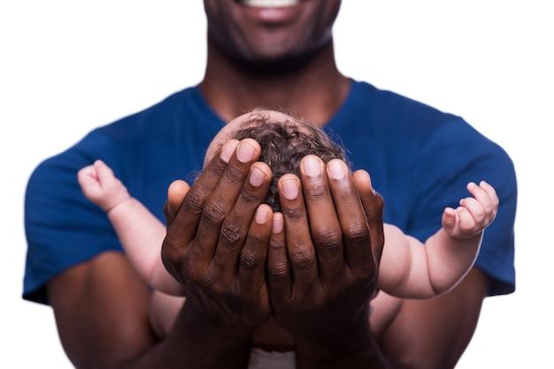 Новая жизнь в его руках. крупный план счастливого молодого африканского человека, держащего своего маленького ребенка и улыбающегося, стоя изолированного на белом