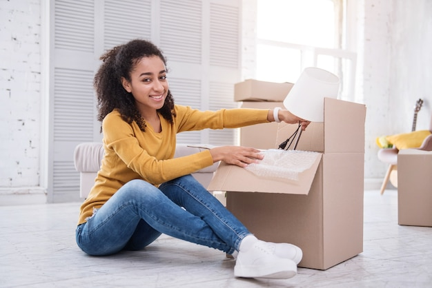New life milestone. upbeat curly-haired girl posing for the camera while sitting on the floor and packing a table lamp into the box