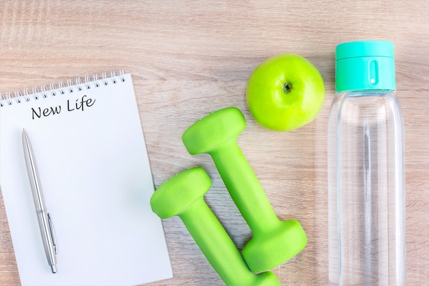 New life written on notebook and dumbbells, fruit, drink water on wooden surface. top view.