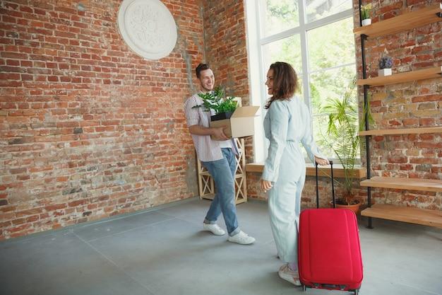 Nuova vita. la giovane coppia si è trasferita in una nuova casa o appartamento. sii felice e fiducioso. famiglia, trasloco, relazioni, concetto di prima casa. disimballare scatole con le loro piante, libri, mettere cose sugli scaffali.