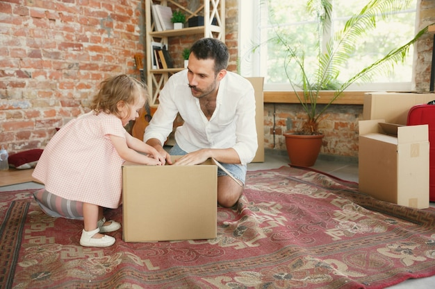 New life. young father and his daughter moved to a new house or apartment. look happy and confident. moving, relations, lifestyle concept. playing together, unpacking boxes and laughting.