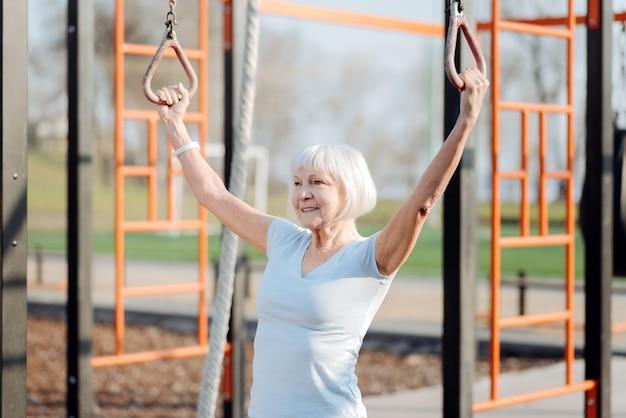 新しいライフスタイル。野外で運動しながらチンアップをしているコンテンツ金髪女性