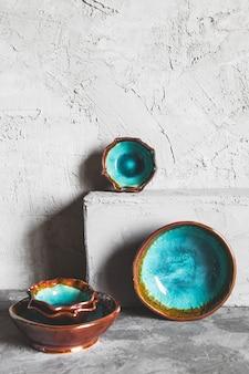 孤立した白い背景の上からの新しい豪華なカトラリービュー。上面図。金の指輪が付いた磁器の青い受け皿。トレンディなプレートパステルカラー。フラットレイビュー。