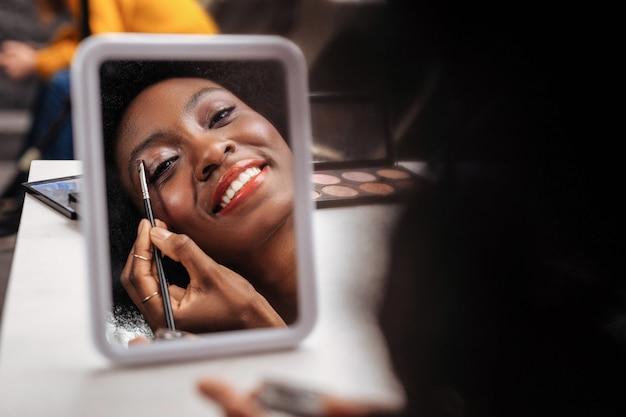 新しいメイク。彼女のまぶたにアイシャドウを置くオレンジ色のトップを着て笑顔のアフリカ系アメリカ人女性 Premium写真