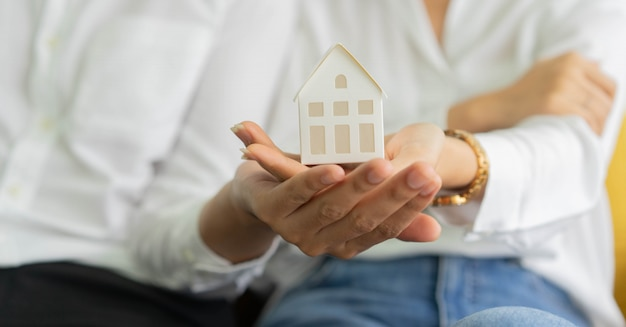 New married couple holding house's model together for home loan and property investment concept