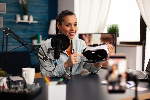New media influencer smiling at camera while recording vr headphones review for followers. creative vlogger making video blog concept speaking and looking at smartphone on tripod home studio podcast