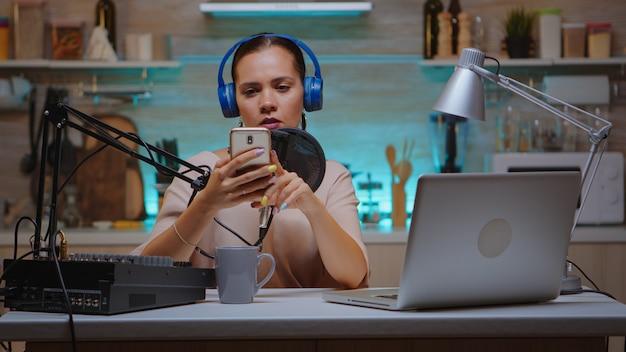 홈 스튜디오에서 스마트폰을 사용하고 동영상 블로그를 녹화하는 뉴미디어 스타. 크리에이티브 온라인 쇼 온에어 프로덕션 인터넷 방송 호스트 스트리밍 라이브 콘텐츠, 디지털 소셜 미디어 커뮤니케이션 녹음