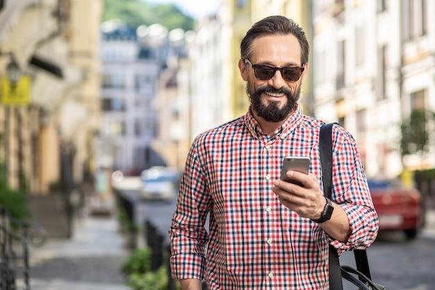 新しいメッセージ。通りに立っている間彼のスマートフォンを使用してうれしそうなひげを生やしたビジネスマン