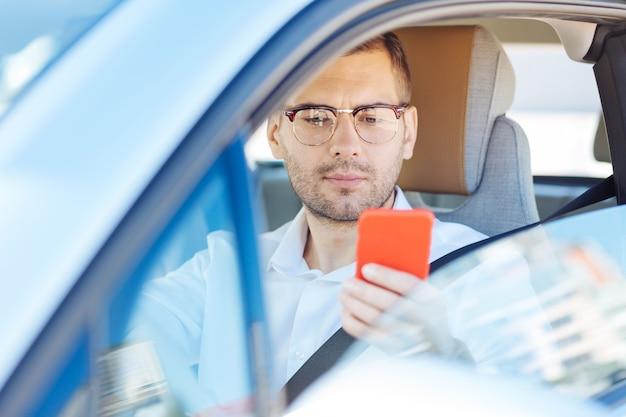 新しいメッセージ。新しいメッセージをチェックしながら彼のスマートフォンを保持している賢い真面目な男