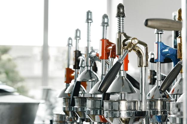 Новые металлические ручные соковыжималки в ряд на полке магазина крупным планом