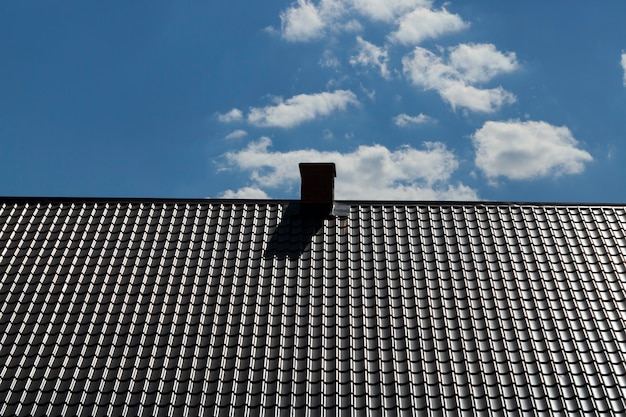 New metal roof with chimney on the background of blue sky,