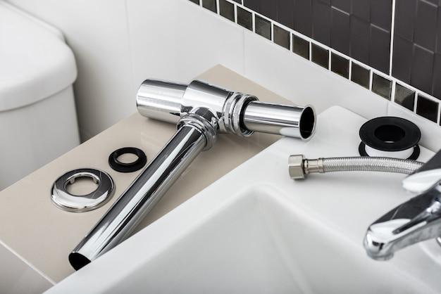 Новый металлический сифон и прочая раковина в ванной.