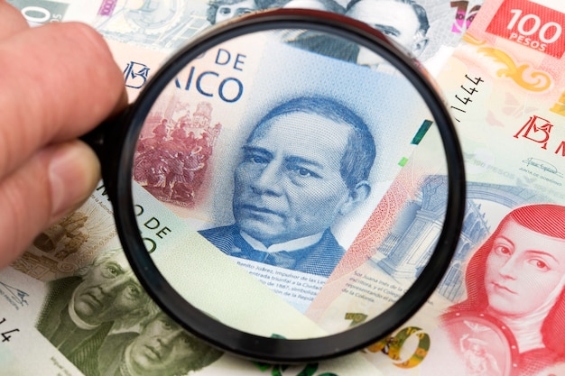 New mexican pesos in a magnifying glass a business background