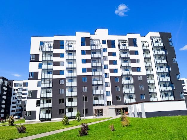 青い空の向かいにある新しいモダンなアパートの建物