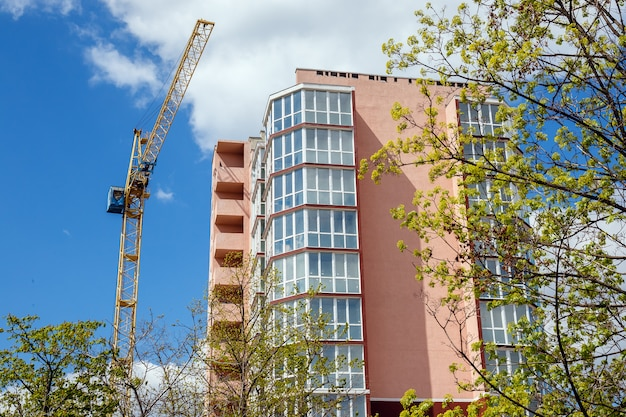 New modern  apartment house and green trees on a background of blue cloudy sky at sunny day.