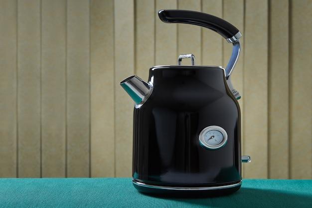 온도계가있는 새로운 현대적인 검은 금속 전기 주전자.