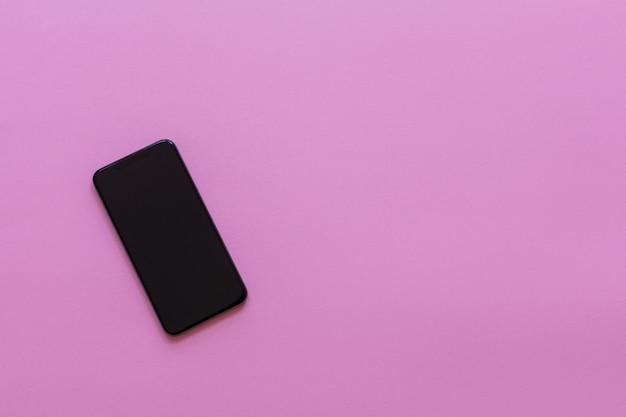 ピンクの背景、フラットレイ、コピースペースの新しいモダンな黒い電話