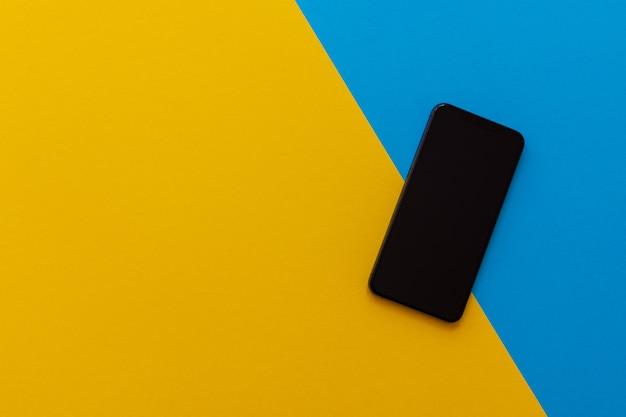 黄色と青の背景、フラットレイ、コピースペースの新しいモダンな黒い電話