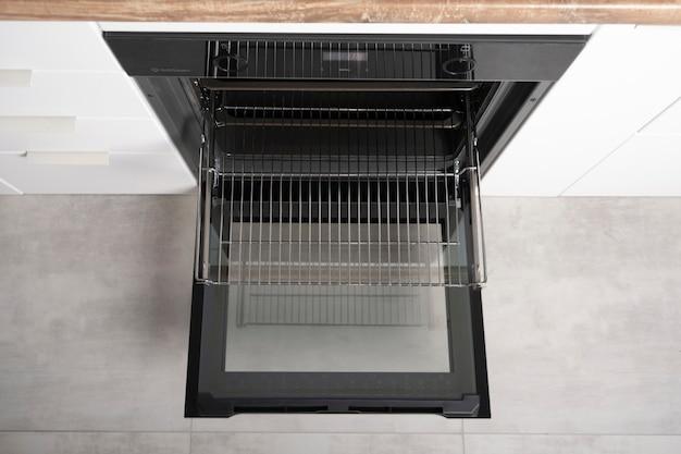 스크린, 컨벤션 및 그릴, 비어 있고 개방 된 검정색으로 제작 된 새로운 현대식 전기 오븐. 텔레스코픽 가이드. 흰색 미니멀리즘 주방의 스칸디나비아 로프트 스타일. 고품질 사진