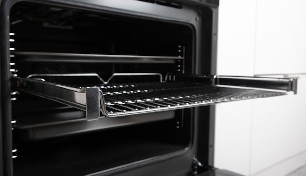 스크린, 컨벤션 및 그릴, 비어 있고 개방 된 검정색으로 제작 된 새로운 현대식 전기 오븐. 텔레스코픽 가이드. 흰색 최소한의 주방에서 스칸디나비아 스타일. 고품질 사진
