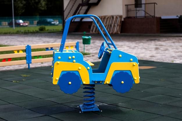明るい日当たりの良い夏の日に柔らかいゴム製の床と保育園の遊び場で春に新しい近代的なプラスチック製の明るいカラフルな青と黄色の大きなおもちゃの車。屋外での子供の活動に最適な場所。