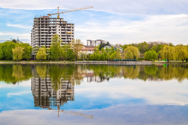 New modern skyscraper under construction on the bank of a lake. concrete building reflection in water