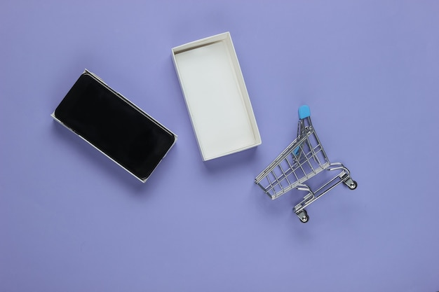 New modern smartphone in box and mini shopping trolley on blue
