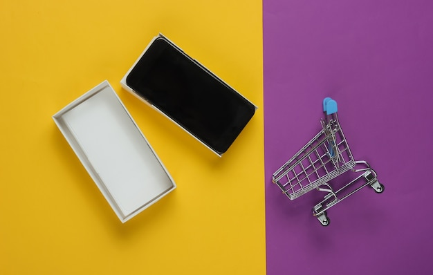 New modern smartphone in box and mini shopping trolley on colored