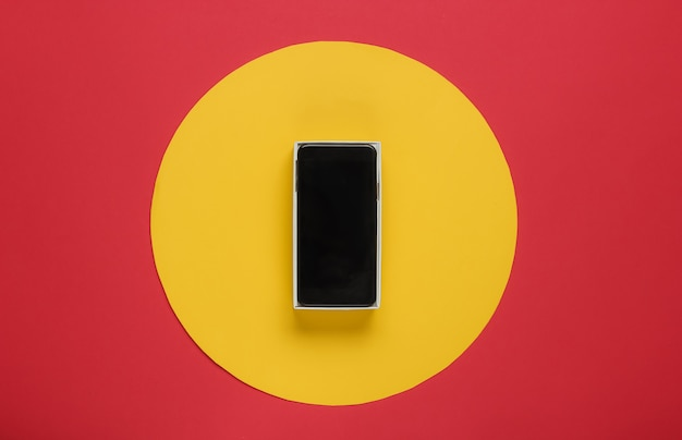 New modern smartphone in box on red with yellow circle in the middle