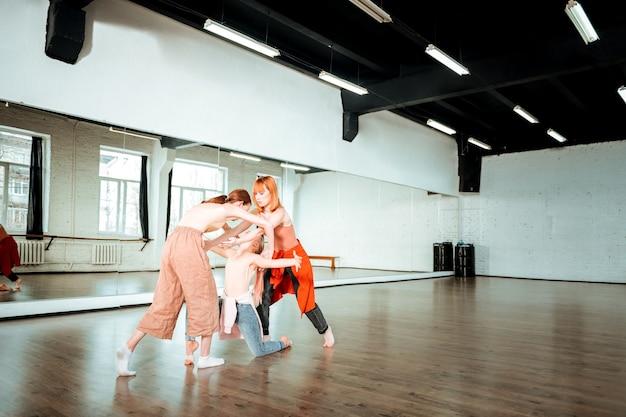 新しい動き。ダンススクールの2人の生徒とジーンズをはいて新しい動きをしている先生